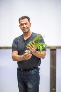 Milo Shammas holding large plant against sky background