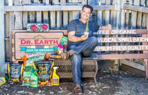 Milo Shammas sitting on bench with products